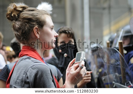 TORONTO-JUNE 26:   An activist taking pictures with her cell phone of the riot police during the G20 Protest on June 26, 2010 in Toronto, Canada. - stock photo