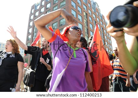 TORONTO-JUNE 25:   An angry afro- american woman chanting slogans in front of a police vehicle during the G20 Protest on June 25, 2010 in Toronto, Canada.
