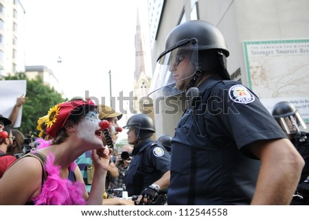 TORONTO-JUNE 25:   Clown dressed activists teasing the police officers during the G20 Protest on June 25  2010 in Toronto, Canada. - stock photo