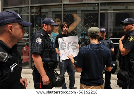 TORONTO-JUNE 27: Group of policemen interrogate protester with sign at G20 protest June 27, 2010 in Toronto. - stock photo