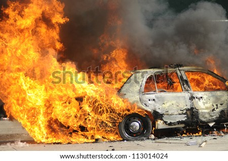 TORONTO-JUNE 26:  Parts of a police car burning after being torched during the G20 Protest on June 26, 2010 in Toronto, Canada. - stock photo