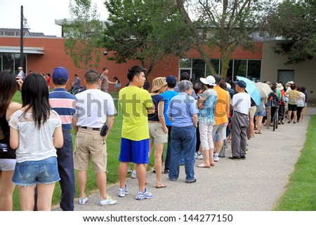 TORONTO - JUNE 23: People lining up in a park in a hot day of Summer on June 23, 2013 in Toronto. Toronto, has a humid continental climate with warm and humid summers. - stock photo
