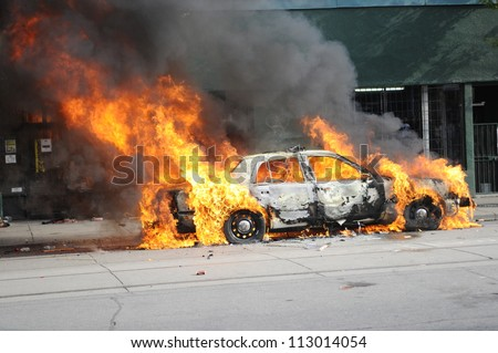 TORONTO-JUNE 26:  Police cars burning during the G20 Protest on June 26, 2010 in Toronto, Canada. - stock photo