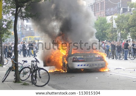 TORONTO-JUNE 26:  Police cars burning on the intersection of queen and spadina while the protesters are gathered around it  during the G20 Protest on June 26, 2010 in Toronto, Canada. - stock photo