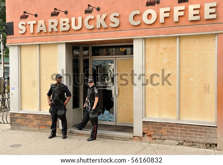 TORONTO-JUNE 27: Police in front of Starbucks Coffee Shop boarded with plywood because window are broken from protesters at G20 the night before on June 27, 2010 in Toronto. - stock photo