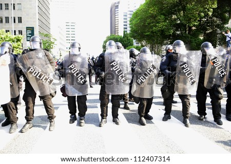 TORONTO-JUNE 25: Police in Riot gear  protecting an intersection during the G20 Protest on June 25, 2010 in Toronto, Canada. - stock photo
