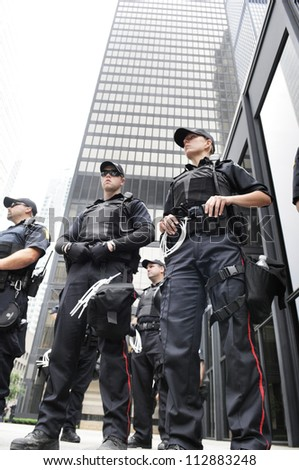 TORONTO-JUNE 27:  Police officers protecting an important financial building  during the G20 Protest on June 27, 2010 in Toronto, Canada. - stock photo