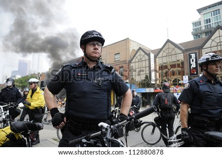 TORONTO-JUNE 26:   Police officers protecting the crime scene after a police patrol car was torched by the vandals during the G20 Protest on June 26, 2010 in Toronto, Canada. - stock photo