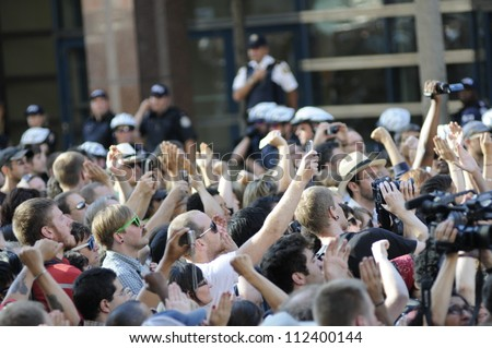 TORONTO-JUNE 28:   Protesters chanting slogans and taking pictures during a protest rally in front of the police headquarter after the G20 summit on June 28, 2010 in Toronto, Canada. - stock photo