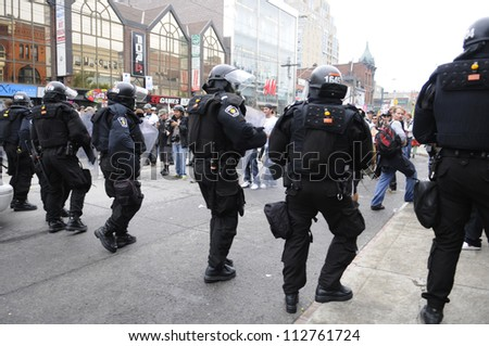 TORONTO-JUNE 26:   Riot police officers approaching the protesters during the G20 Protest on June 26 2010 in Toronto, Canada. - stock photo