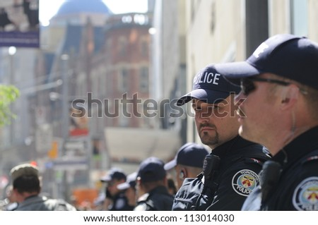 TORONTO-JUNE 25:  Toronto police cops keeping an eye on the mob while standing on the sidewalk during the G20 Protest on June 25, 2010 in Toronto, Canada.