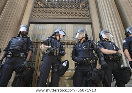 TORONTO-JUNE 25:  Toronto Police officers in riot gear guarding the entrance of a  financial building during the G20 Protest on June 25, 2010 in Toronto, Canada. - stock photo
