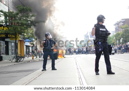TORONTO-JUNE 26:   Toronto police officers surrounding a torched police car while the people watches on during the G20 Protest on June 26, 2010 in Toronto, Canada. - stock photo