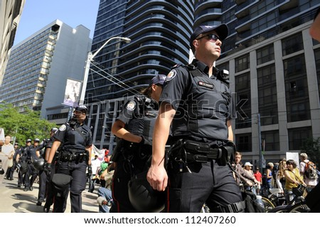 TORONTO-JUNE 25: Toronto police  walking on the sidewalks as the rally take control of the streets during the G20 Protest on June 25, 2010 in Toronto, Canada. - stock photo