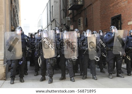 TORONTO-JUNE 25:  Toronto Riot Police restricting protesters from entering an alley between two financial buildings during the G20 Protest on June 25, 2010 in Toronto, Canada. - stock photo
