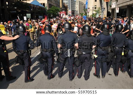 TORONTO-JUNE 25: Toronto Riot Police standing in front of protesters on June 25, 2010 in Toronto, Canada. - stock photo