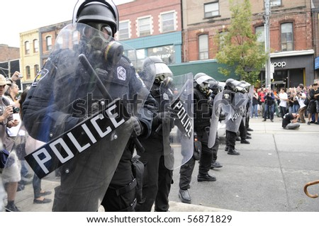 TORONTO-JUNE 26:  Toronto Riot Police  wearing gas masks restricting the protesters on Queen Street during the G20 Protest on June 26, 2010 in Toronto, Canada.