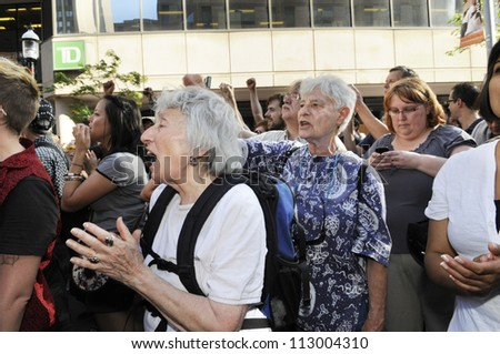 TORONTO-JUNE 28:   Two old female supporters clapping and shouting amongst a crowd during the G20 Protest on June 28, 2010 in Toronto, Canada. - stock photo
