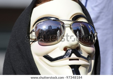 TORONTO - MARCH 11:   A guy with a guy fawkes mask listening to the speakers  during  a  protest against an election fraud from last year'Â?Â?s federal election on March 11 2012 in Toronto, Canada. - stock photo