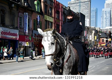 TORONTO - MARCH 17: Mounted policewoman marches on the street. Toronto's annual St. Patrick's Day parade takes place under sunny skies on Sunday afternoon March 17, 2013.