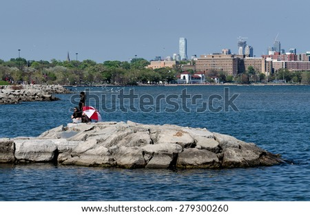 TORONTO - MAY 17: People and birds are congregating around Sunnyside Beach and Pavillion at Lake Ontario in Toronto's west end on May 17, 2015    - stock photo