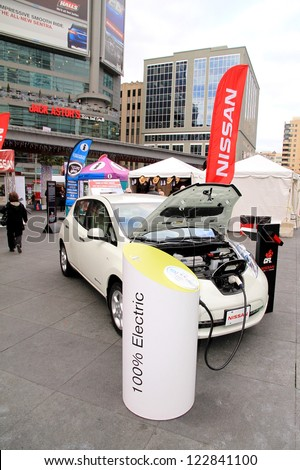 TORONTO - NOVEMBER 23: A street event promoting a 100% electric Nissan car on November 23, 2012 in Toronto. Over 4.6 of Nssan vehicles were sold globally in the year 2011. - stock photo