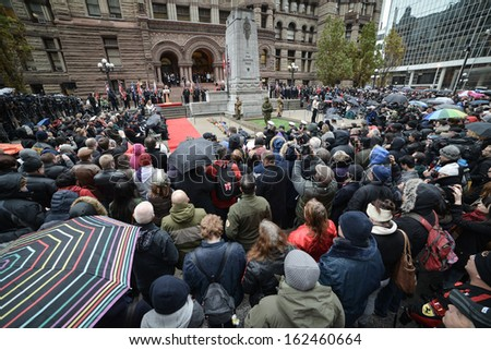 TORONTO - NOVEMBER 11: People attend Remembrance Day Services at Old City Hall Cenotaph in Toronto on November 11, 2013.