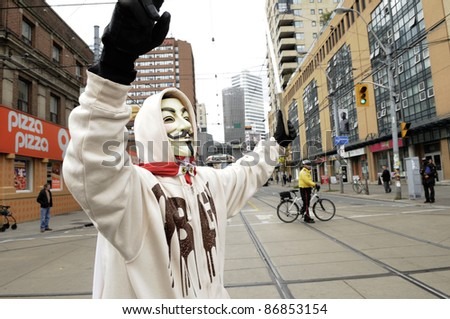 TORONTO - OCTOBER 17: A protestor wearing a guy fawkes mask walking in a rally  during the Occupy Toronto Movement on October 17, 2011 in Toronto, Canada. - stock photo
