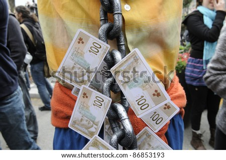 TORONTO - OCTOBER 17:  A protestor wearing a  metal chain which is changed with $ 100 bills during the Occupy Toronto Movement on October 17, 2011 in Toronto, Canada. - stock photo