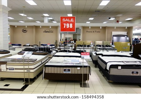 TORONTO - OCTOBER 4: Mattresses on sale at the Hudson's Bay on October 4, 2013 in Toronto. Hudson's Bay is a chain of 90 department stores that operate across parts of Canada. - stock photo
