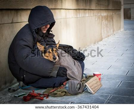 TORONTO, ONTARIO, CANADA - January 23, 2016: A homeless man and his homeless dog beg for small change outside Union Station, Toronto's main train station.  - stock photo