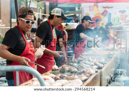 TORONTO,ONTARIO-JULY 5,2015: Charcoal cooking chicken in street food stand in  St. Clair Ave West is the largest Hispanic festival in Canada gathering thousands every year. - stock photo