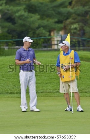 TORONTO, ONTARIO - JULY 21: U.S. golfer John Mallinger talking with his caddy during a pro-am event at the RBC Canadian Open golf on July 21, 2010 in Toronto, Ontario. - stock photo