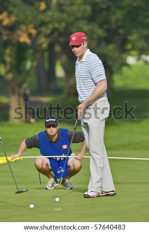 TORONTO, ONTARIO - JULY 21: U.S. golfer Ricky Barnes with his caddy during a pro-am event at the RBC Canadian Open golf on July 21, 2010 in Toronto, Ontario. - stock photo