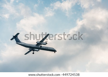 TORONTO - SEPTEMBER 7: Low-angle view of a Porter Airlines Bombardier Dash-8 against a cloudy sky, initiating its descent towards Billy Bishop Toronto City Airport, on September 7, 2015. - stock photo
