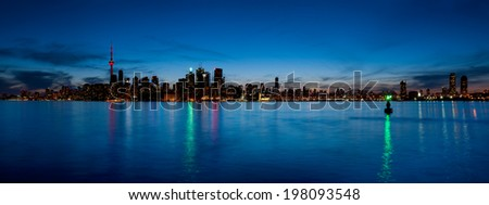 Toronto skyline panorama at dusk over lake with colorful lights - stock photo