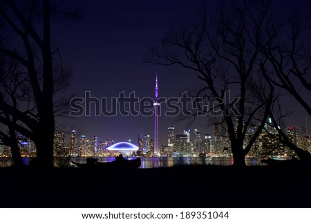 toronto skyline with silhouetted trees in foreground - stock photo