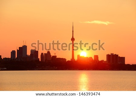 Toronto sunrise silhouette over lake with red tone. - stock photo