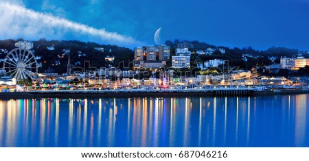 Torquay Promenade from a distance at night, with illuminated lights and the moon peeping over the horizon, with light reflection in the blue sea.  Torquay, dEVON