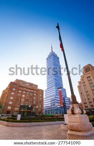 Torre Latinoamericana or tower of Latino America and other buildings and Mexican flag on Juarez avenue and morning sun flare, Mexico city capital  - stock photo
