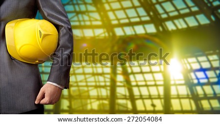 torso engineer or worker hand holding yellow helmet for workers against blue transparent glass office window and sunset light with rays background Empty texture space for inscription - stock photo