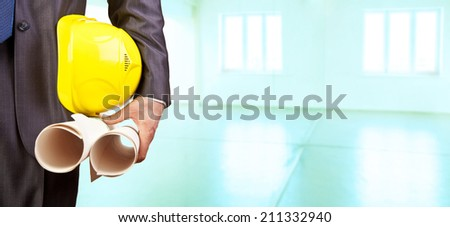 torso engineer or worker hand holding yellow helmet for workers security on  background of new empty apartment buildings with glass windows roof floor and door of blue - stock photo