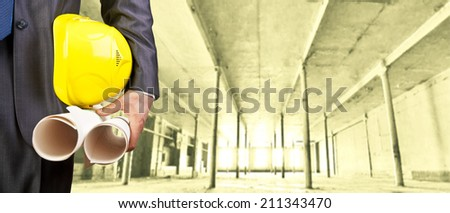 torso engineer or worker hand holding yellow helmet for workers security over empty room indoor old building inside warehouse background Copy Space for inscription - stock photo