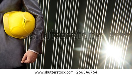 torso engineer or worker hand holding yellow helmet for workers security over sun light rays between jalousie office window background Empty space for inscription against sunset  - stock photo