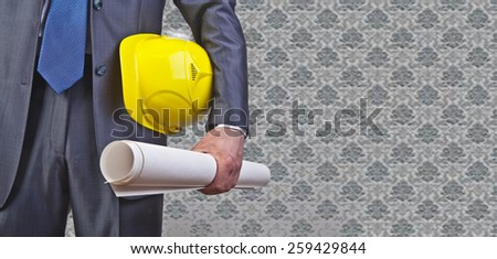 Torso engineer, worker or architect holding in hand blueprint and yellow plastic helmet hardhat on textured  wall with gray wallpaper background Empty copy space for inscription - stock photo