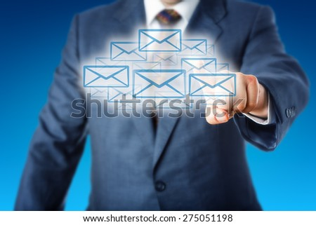 Torso of a white collar worker stretching his left index finger to touch email icons shaping a cloud. Blue business suit and sky blue background. Metaphor for cloud computing and instant email access. - stock photo
