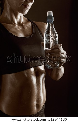 Torso of a young athletic woman holding a bottle of water on a dark background