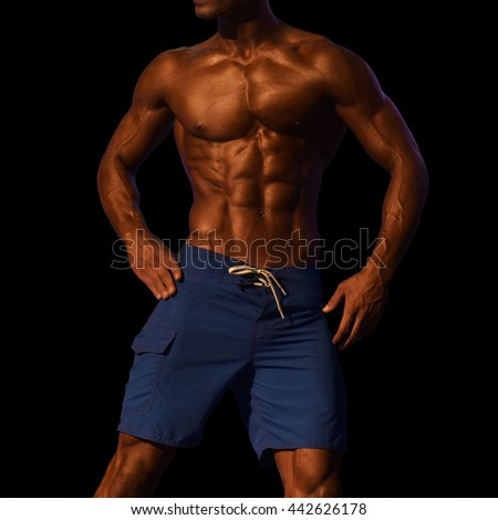 torso of attractive male body builder isolated on black background. This has clipping path. - stock photo