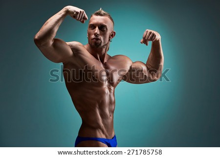 torso of attractive male body builder on blue background. - stock photo