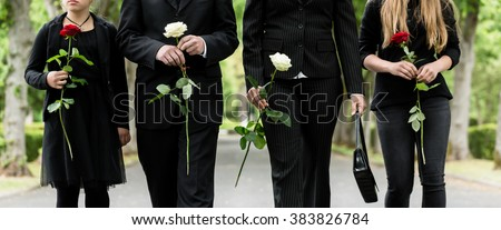 Torso of family on cemetery mourning holding red and white roses in hands - stock photo